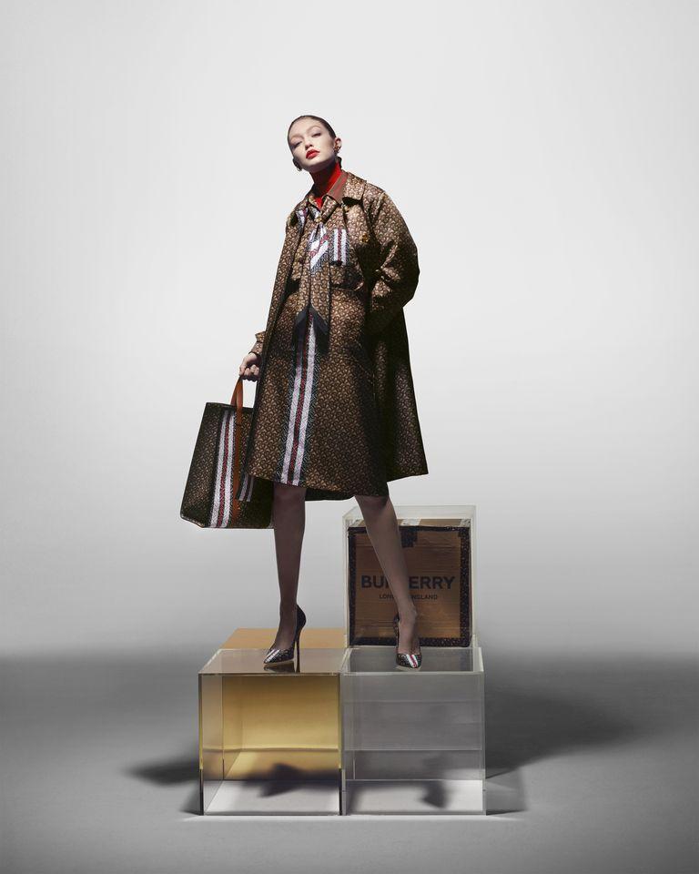 dengan setelan suit dan padded coat bermotif Burberry, dipadu bersama sepatu pantofel resmi.