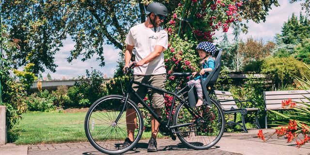 man holding his bike with his young daughter on bike seat outside