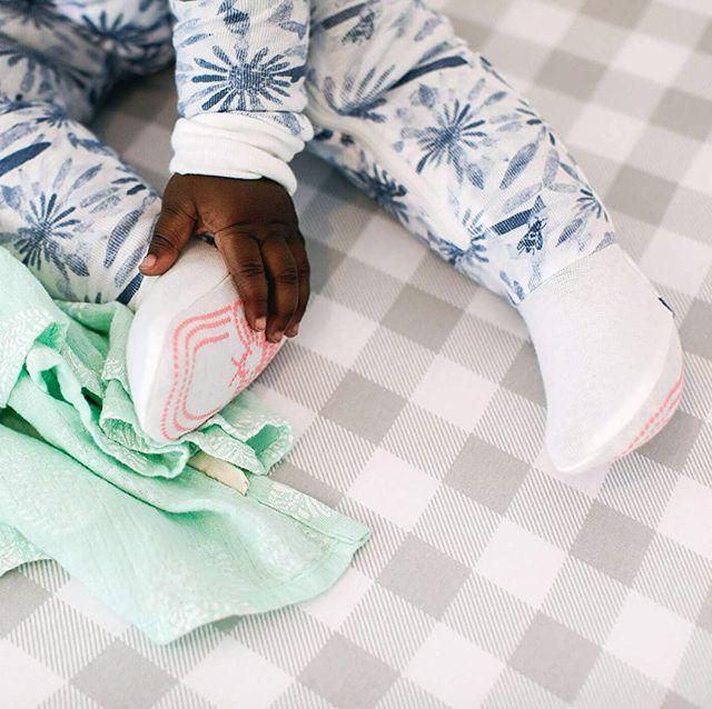 baby sitting on plaid crib sheet