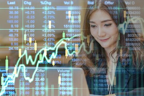 business financial conceptม double exposure of happy asian businesswoman sitting on working space and looking the stock market exchange information and trading graph in the modern office