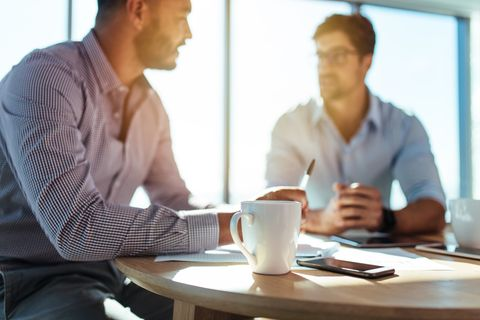 Business investors discussing business matters sitting at table in office.
