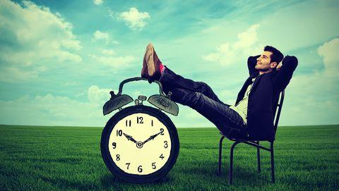 Relaxte man in pak met klok