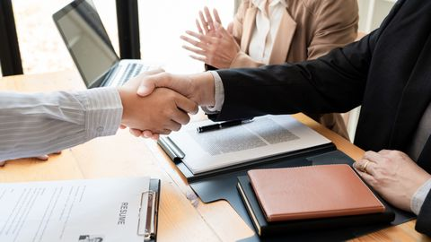 business people shaking hands while interviewing candidate with colleague clapping in background at table