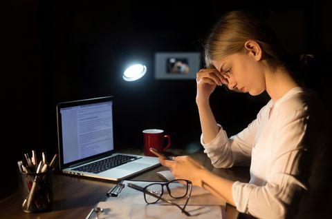 business woman headache on smartphone working at night
