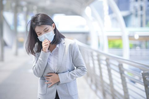 business woman wear face mask and coughing while standing in the town