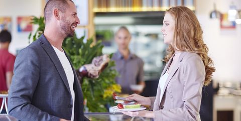Businessman and businesswoman having fruit from salad bar