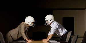 Businessman and businesswoman in face-off wearing football helmets