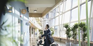 Businessman commuter with bicycle talking on smart phone, waiting at elevator in office lobby