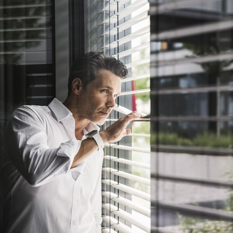 businessman peeking through sunblinds at the window in office