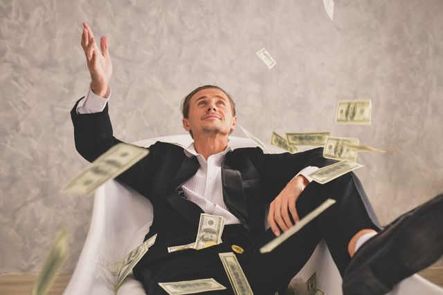 businessman playing with paper currency while sitting on chair in office