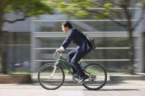Businessman riding bike, side view