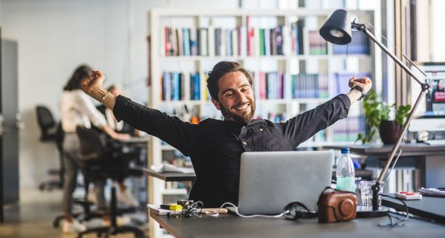 businessman sitting with arms outstretched at desk in office