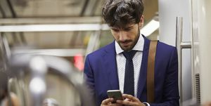 Businessman using cell phone on subway train