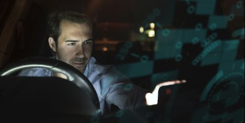 Businessman using device in car at night surrounded by data
