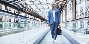 Businessman walking on moving walkway