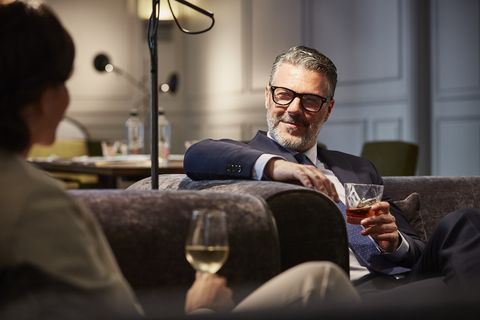 Businessman with a drink sitting in hotel