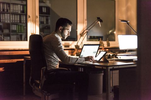 Businessman working at desk in office at night