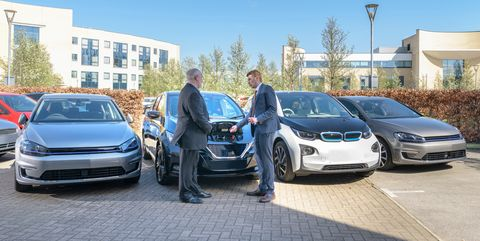 businessmen looking at range of electric cars in business park