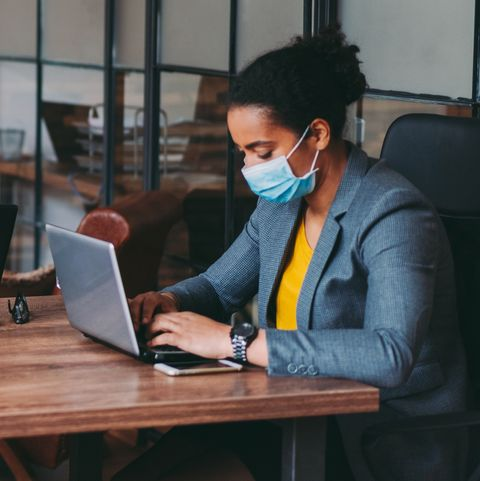 businesspeople working with face masks in the office during covid 19 pandemic