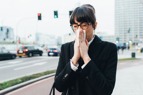 Businesswoman blowing nose on busy road, Milan, Italy