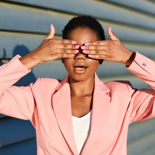 businesswoman covering eyes while standing against wall