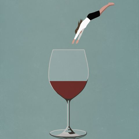 businesswoman diving into large glass of wine