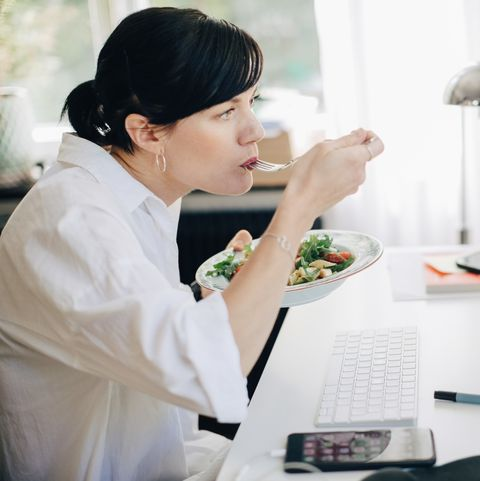 businesswoman eating pasta while looking at computer in home office