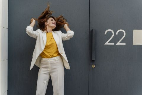 businesswoman in white pant suit, standing in front of entrance door