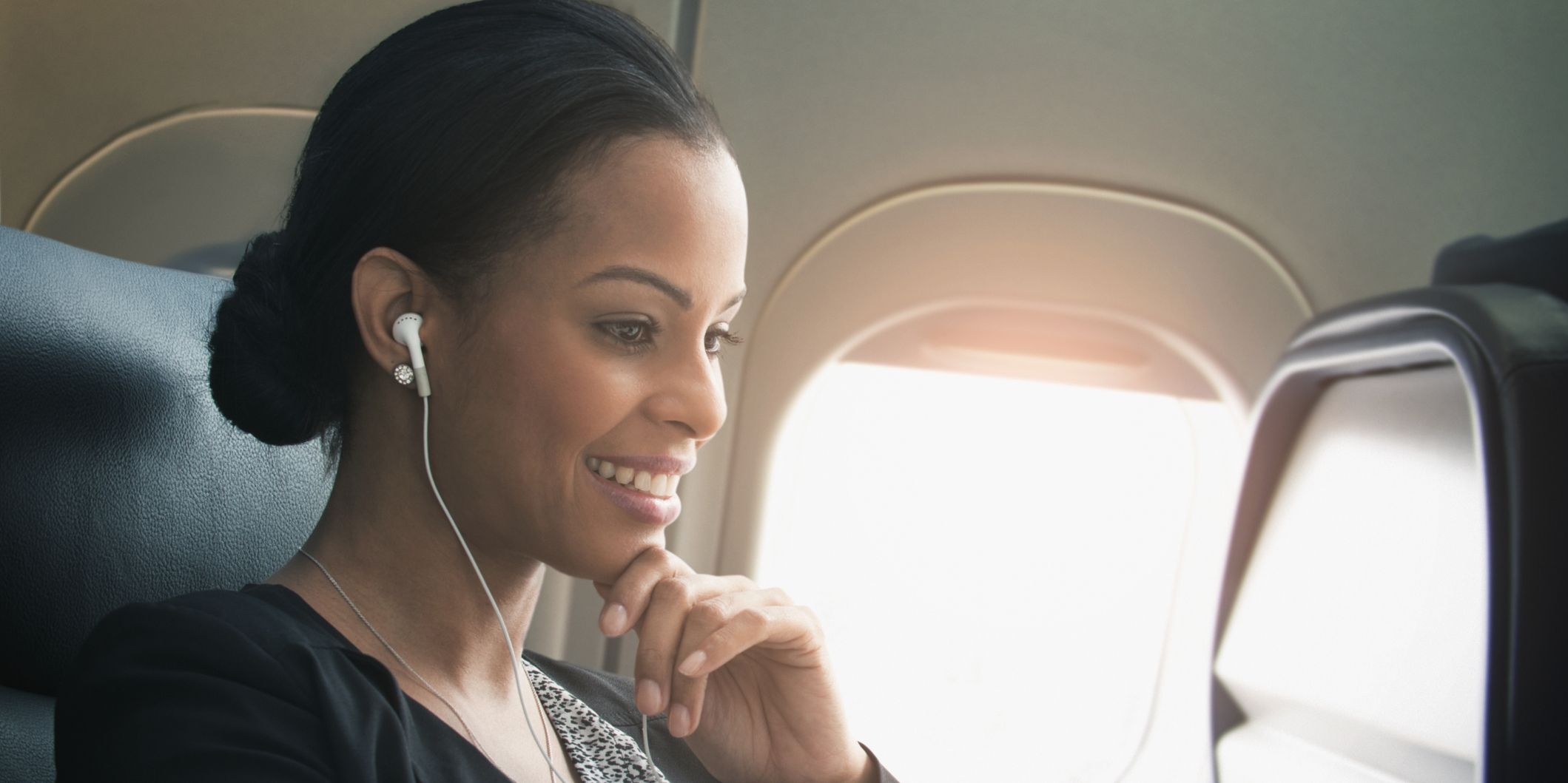 Businesswoman listening to earbuds on airplane