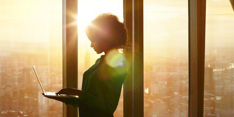 businesswoman on laptop at window in morning sun