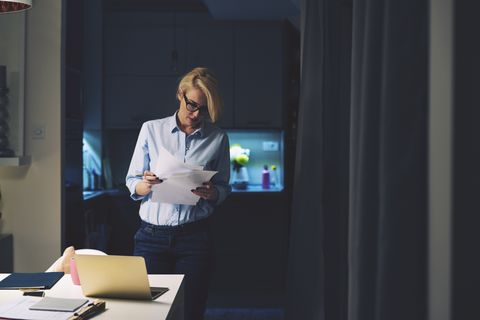 businesswoman reading documents while standing by desk in home office