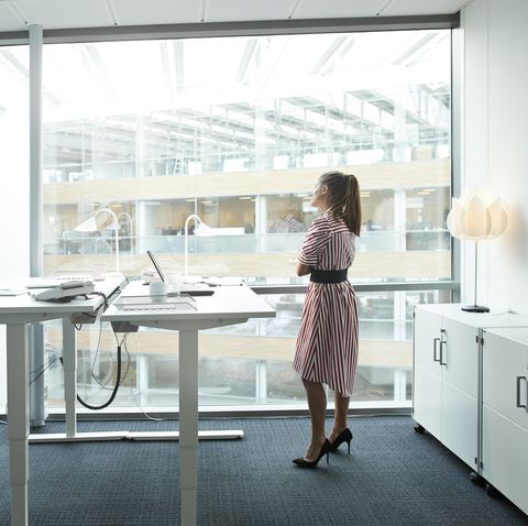 businesswoman standing in modern office and looking out of big windows