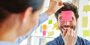 Businesswoman Sticking Adhesive Note On Colleague Forehead In Office
