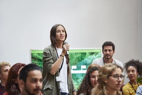 Businesswoman talking into microphone in seminar