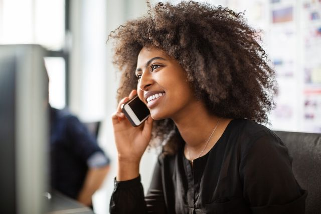 Businesswoman using cell phone at her desk