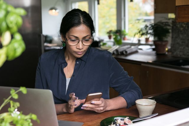 businesswoman using mobile phone with laptop on table in home office