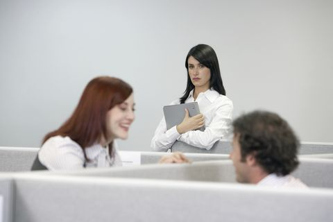 Businesswoman watching two coworkers talking over cubicle wall