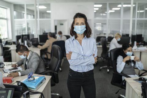 una mujer de negocios, con mascarilla, en una oficina