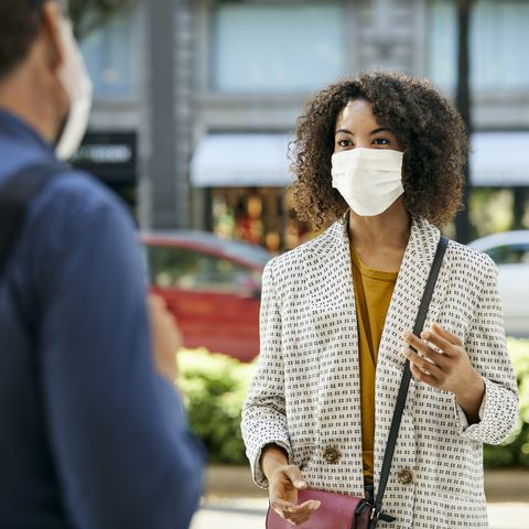 businesswoman wearing protective face mask talking to male coworker during covid9 pandemic in city