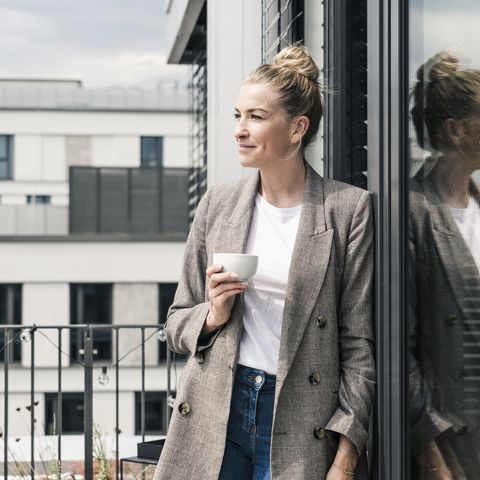 businesswoman with coffee cup standing on roof terrace