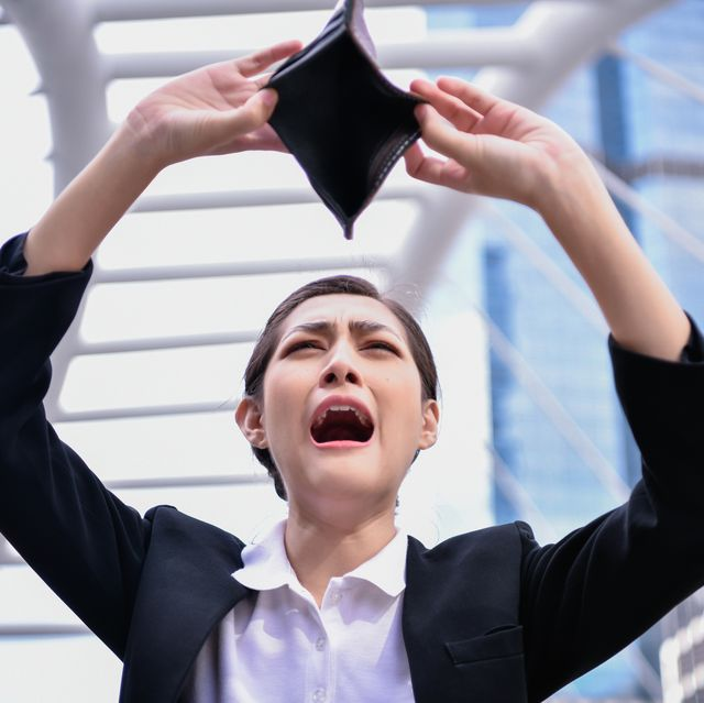 businesswoman with empty purse crying while standing against buildings in city
