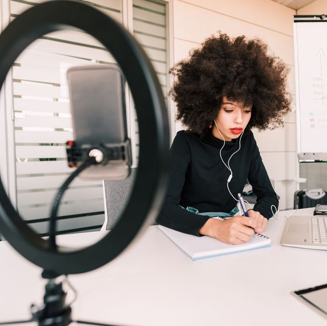 businesswoman working, making notes, surrounded by tech