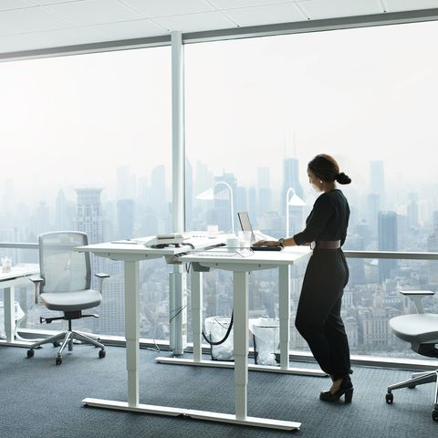 businesswoman working on computer in office with beautiful view of skyline