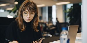 Businesswoman writing while holding mobile phone at desk in office