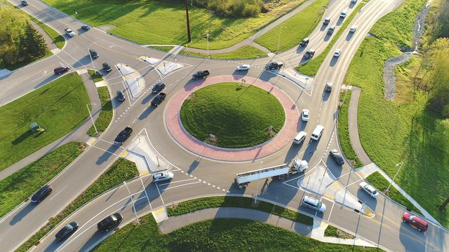 busy city roundabout intersection at sunrise rush hour