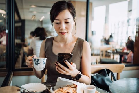 busy young asian businesswoman checking emails and handling work issues on smartphone while sitting in a restaurant, having a quick lunch in the middle of a work daybusiness on the go