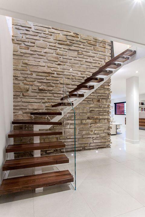 Escalera con peldaños volados en madera y barandilla de cristal