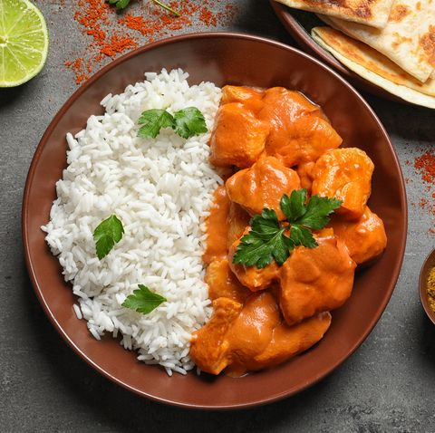 Butter chicken with rice served on grey table, flat lay