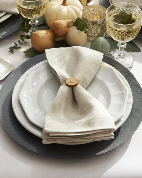 button napkin ring threaded with twine tied on a neutral tone napkin