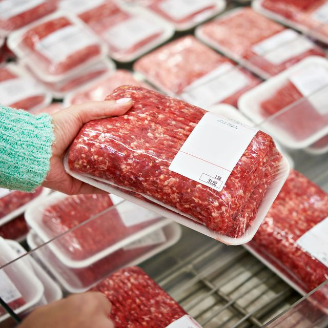 buyer woman chooses chopped meat in shop